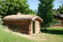 Log cabin with sod roof.